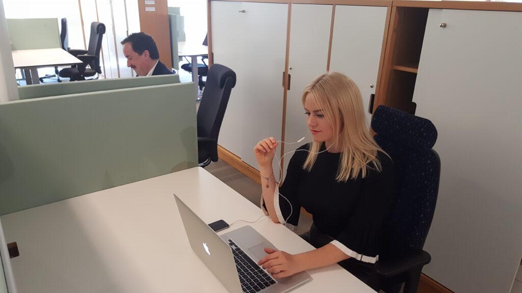 arbetande kvinna i öppet kontorslandskap